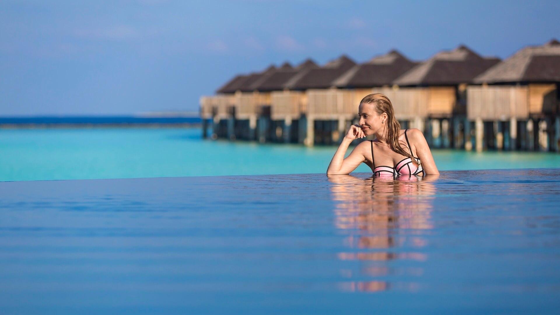 The Sun Siyam Irufushi 5* - Vista di una donna appoggiata al bordo della piscina che guarda l'orizzonte